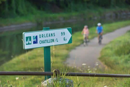 Cyclotouristes et panneau de La Loire à vélo près de l'écluse du canal latéral à la Loire, à Beaulieu-sur-Loire